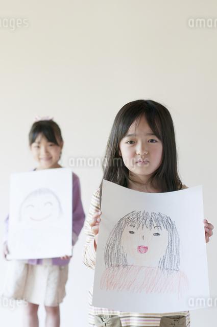 自分の描いた絵を見せる2人の女の子のイラスト素材 [FYI04545535]