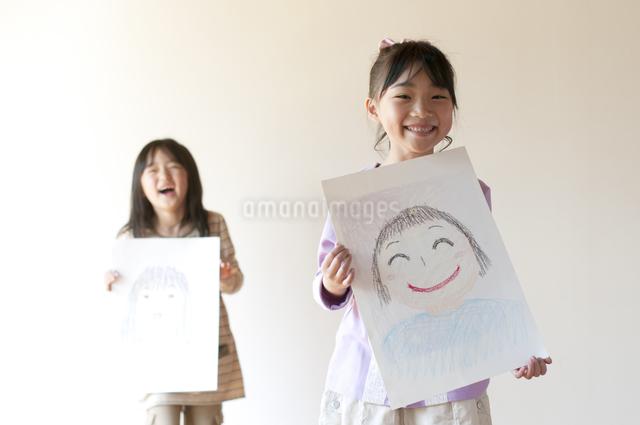 自分の描いた絵を見せる2人の女の子のイラスト素材 [FYI04545573]