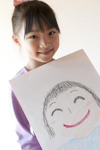 自分の描いた絵を見せる女の子のイラスト素材 [FYI04545579]