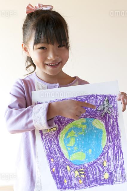 自分の描いた絵を見せる女の子のイラスト素材 [FYI04545580]