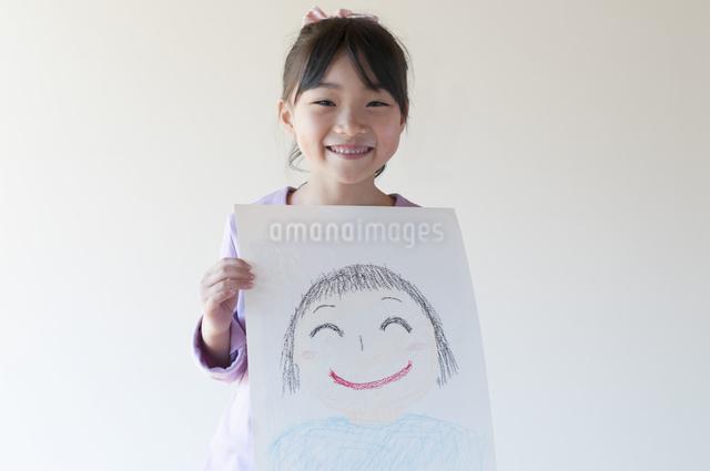 自分の描いた絵を見せる女の子のイラスト素材 [FYI04545601]