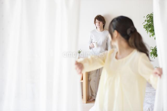 部屋のカーテンを開ける女性とコーヒーカップを持つ男性の写真素材 [FYI04545604]
