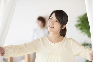 部屋のカーテンを開ける女性の写真素材 [FYI04545605]