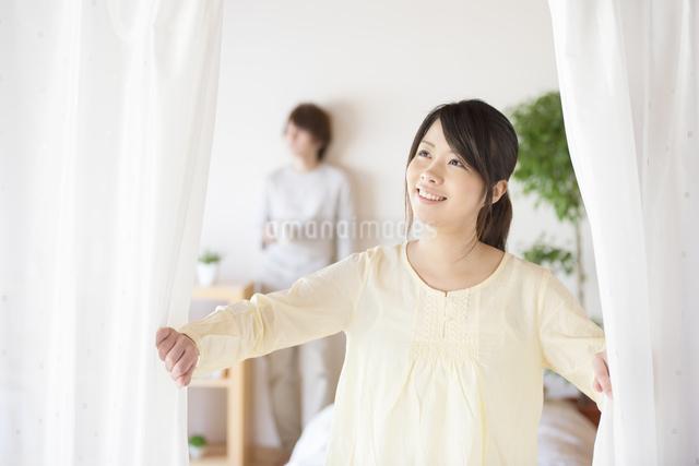 部屋のカーテンを開ける女性の写真素材 [FYI04545606]