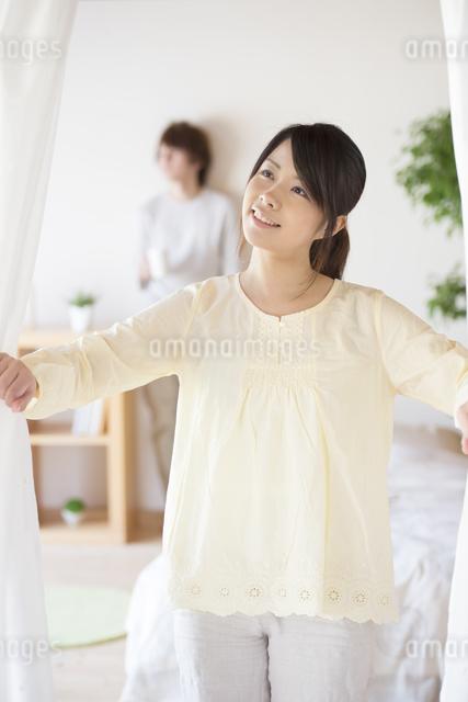 部屋のカーテンを開ける女性の写真素材 [FYI04545607]