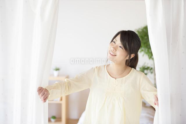 部屋のカーテンを開ける女性の写真素材 [FYI04545608]
