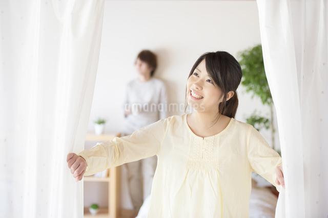 部屋のカーテンを開ける女性の写真素材 [FYI04545609]