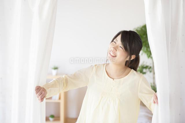 部屋のカーテンを開ける女性の写真素材 [FYI04545610]