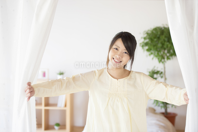 部屋のカーテンを開ける女性の写真素材 [FYI04545611]