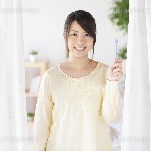 歯ブラシを持ち微笑む女性の写真素材 [FYI04545616]