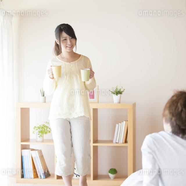 男性にコーヒーを運ぶ女性の写真素材 [FYI04545621]