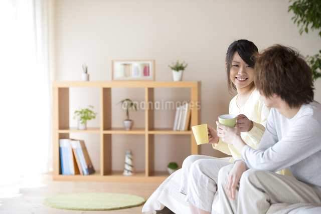 コーヒーを渡すカップルの写真素材 [FYI04545624]