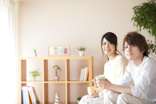 コーヒーカップを持ち微笑むカップルの写真素材 [FYI04545630]