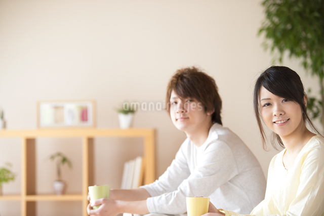 コーヒーカップを持ち微笑むカップルの写真素材 [FYI04545632]