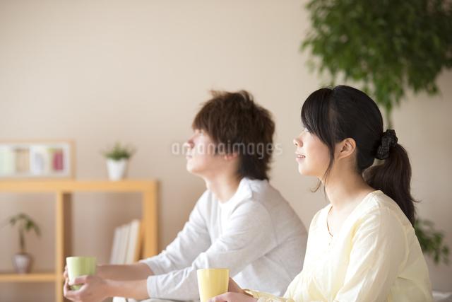 コーヒーカップを持つカップルの写真素材 [FYI04545633]