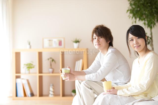 コーヒーカップを持ち微笑むカップルの写真素材 [FYI04545634]