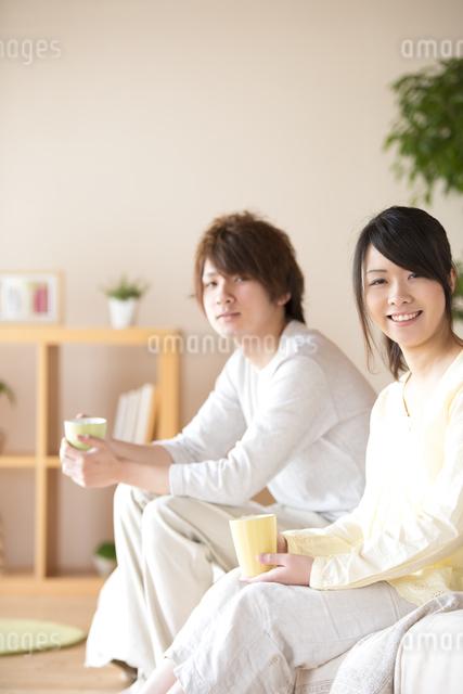 コーヒーカップを持ち微笑むカップルの写真素材 [FYI04545635]