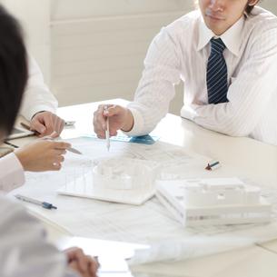 打合せをするビジネスマンとビジネスウーマンの手元の写真素材 [FYI04545917]