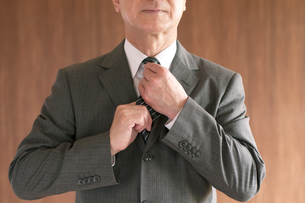 ネクタイを締め直すビジネスマンの手元の写真素材 [FYI04546050]