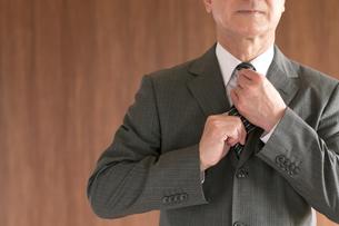 ネクタイを締め直すビジネスマンの手元の写真素材 [FYI04546052]
