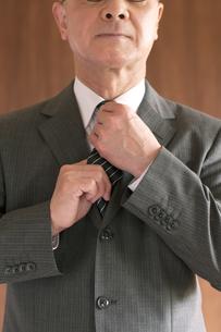 ネクタイを締め直すビジネスマンの手元の写真素材 [FYI04546054]