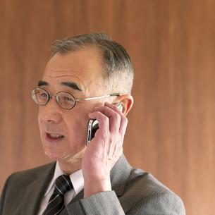 スマートフォンで電話をするビジネスマンの写真素材 [FYI04546056]