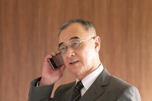 スマートフォンで電話をするビジネスマンの写真素材 [FYI04546057]