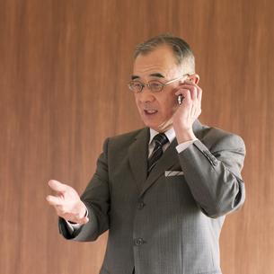 スマートフォンで電話をするビジネスマンの写真素材 [FYI04546066]