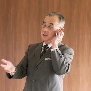 スマートフォンで電話をするビジネスマンの写真素材 [FYI04546067]