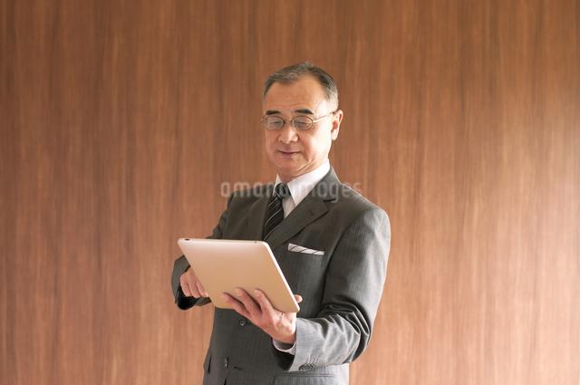 タブレットPCを持つビジネスマンの写真素材 [FYI04546082]