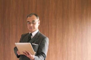タブレットPCを持つビジネスマンの写真素材 [FYI04546087]