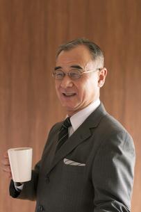 コーヒーカップを持つビジネスマンの写真素材 [FYI04546096]