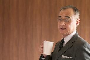 コーヒーカップを持つビジネスマンの写真素材 [FYI04546103]