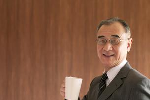コーヒーカップを持つビジネスマンの写真素材 [FYI04546105]