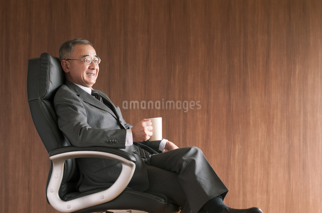 椅子に座りコーヒーカップを持つビジネスマンの写真素材 [FYI04546136]