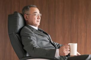 椅子に座りコーヒーカップを持つビジネスマンの写真素材 [FYI04546140]