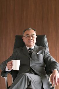 椅子に座りコーヒーカップを持つビジネスマンの写真素材 [FYI04546142]