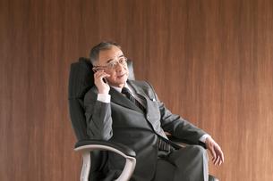 椅子に座りスマートフォンで電話をするビジネスマンの写真素材 [FYI04546150]