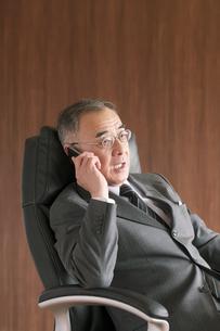 椅子に座りスマートフォンで電話をするビジネスマンの写真素材 [FYI04546156]
