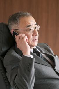 椅子に座りスマートフォンで電話をするビジネスマンの写真素材 [FYI04546160]