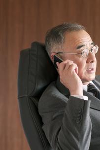 椅子に座りスマートフォンで電話をするビジネスマンの写真素材 [FYI04546162]