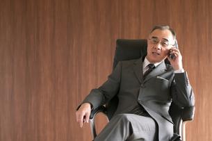 椅子に座りスマートフォンで電話をするビジネスマンの写真素材 [FYI04546166]