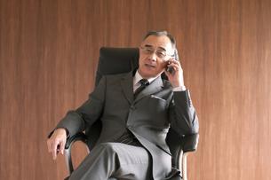 椅子に座りスマートフォンで電話をするビジネスマンの写真素材 [FYI04546167]