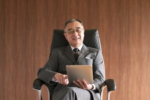 椅子に座りタブレットPCを操作するビジネスマンの写真素材 [FYI04546174]