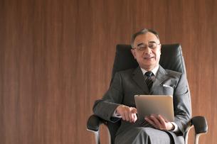 椅子に座りタブレットPCを操作するビジネスマンの写真素材 [FYI04546176]