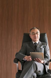 椅子に座りタブレットPCを操作するビジネスマンの写真素材 [FYI04546177]