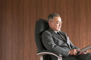 椅子に座りタブレットPCを操作するビジネスマンの写真素材 [FYI04546181]
