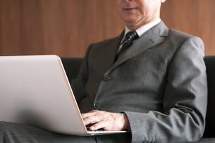 ソファーに座りノートパソコンを操作するビジネスマンの写真素材 [FYI04546206]