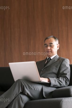 ソファーに座りノートパソコンを操作するビジネスマンの写真素材 [FYI04546209]