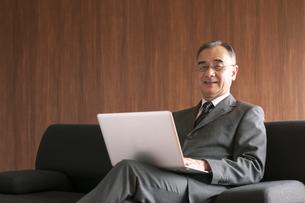 ソファーに座りノートパソコンを操作するビジネスマンの写真素材 [FYI04546213]